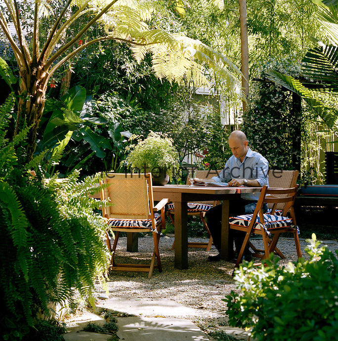 Owner and designer Moises Esquenazi sits in the secluded rear garden of his Los Angeles home