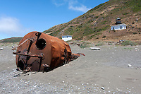 A rusted navigation buoy lies on the beach with the decommissioned Punta Gorda Lighthouse in the background on Northern California's Lost Coast south of Cape Mendocino. The Punta Gorda Lighthouse was active from 1912 until it was deemed no longer necessary in 1951. Photographed 07/08