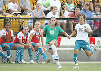 Heather O'Reilly #10 of Abby's XI sends a cross over past Aya Miyama #24 of Marta's XI in front of the subs bench of Marta's team during the WPS All-Star game at KSU Stadium in Kennesaw, Georgia on June 30 2010. Marta XI won 5-2.
