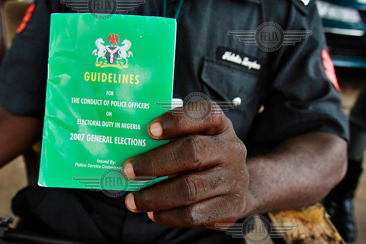 A policeman shows the guidelines for police officers on election day while guarding the INEC (Independent National Electoral Commission) office.