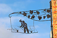 A wrought iron painted sign that illustrates the theme of champagne and wine production: black sign showing a man doing pruning and training of the vines and a vine with leafs and grape bunches,, the village of Hautvillers in Vallee de la Marne, Champagne, Marne, Ardennes, France