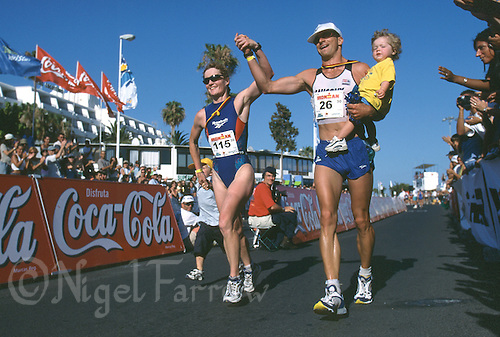 26 MAY 2001 -  LANZAROTE, CANARY ISLANDS - Heike Funk and her husband Harald Funk finish together accompanied by their children at the 2001 Ironman Lanzarote event. Heike Funk was later disqualified. (PHOTO (C) NIGEL FARROW)