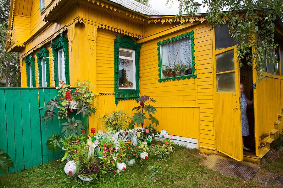 Korovikha, Ivanova Region, Russia, 05/08/2012..A woman peers through the open front door of a traditional brightly painted Russian wooden home in Korovikha, some 200 miles east of Moscow.