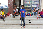 Youth with Superman T-shirt, Punakha town centre with a mix of traditional and modern lifestyles, Bhutan..Bhutan the country that prides itself on the development of 'Gross National Happiness' rather than GNP. This attitude pervades education, government, proclamations by royalty and politicians alike, and in the daily life of Bhutanese people. Strong adherence and respect for a royal family and Buddhism, mean the people generally follow what they are told and taught. There are of course contradictions between the modern and tradional world more often seen in urban rather than rural contexts. Phallic images of huge penises adorn the traditional homes, surrounded by animal spirits; Gross National Penis. Slow development, and fending off the modern world, television only introduced ten years ago, the lack of intrusive tourism, as tourists need to pay a daily minimum entry of $250, ecotourism for the rich, leaves a relatively unworldly populace, but with very high literacy, good health service and payments to peasants to not kill wild animals, or misuse forest, enables sustainable development and protects the country's natural heritage. Whilst various hydro-electric schemes, cash crops including apples, pull in import revenue, and Bhutan is helped with aid from the international community. Its population is only a meagre 700,000. Indian and Nepalese workers carry out the menial road and construction work.
