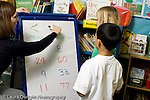 """Education Elementary school Grade 1 mathematics female teacher demonstrating """"greater than"""" """"less than"""" activity on dry erase board to two students one boy and one girl horizontal"""