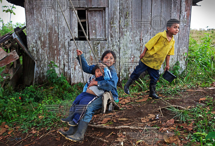 Children play, including two playing on a swing, in an indigenous village in the rainforest.