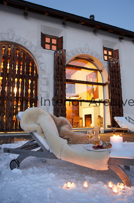 A sun lounger on the snow-covered deck has layers of fur to ward off the cold whilst enjoying a candlelit aperatif