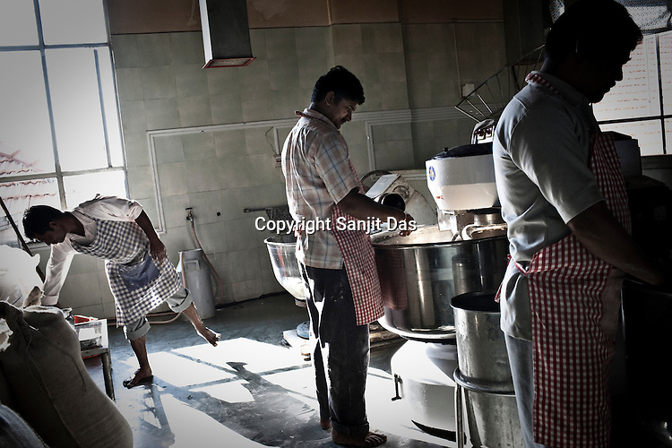 Volunteers and contract labourers are seen kneading flour for rotis (Indian bread) in the kitchen of the Sai Prasadalaya in Shirdi, Maharashtra, India. The Prasadalaya feeds an approximate number of 30000 Sai Baba devotees as a Prasad (holy meal) every day. Free Prasad meals are served to all the devotees. An approximate number of 1000 devotees are served everyday with this facility. Expenses for a plate of Prasad meal  is around Rs. 15/- but the Saibaba Sansthan provides prasad meals to all Sai devotees to Rs. 6/- only. The prasadalaya at the Shirdi Sai Baba Shrine is powered by a large array of concave mirrors that transform sunlight to energy to create hot water and steam for the cooking process. Photograph: Sanjit Das