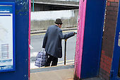 Elderly man carrying a bag uses a handrail on some steps at Hendon station, London.