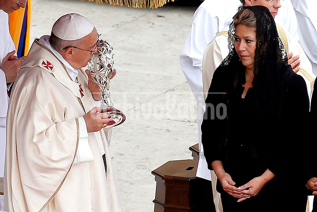 Costa Rican Floribeth Mora Diaz, who claims she was cured of a serious brain condition by a miracle attributed to Pope John Paul II,  bring the relic to Pope Francis during the canonisation mass of Popes John Paul II and John XXIII in St Peter's  Square on April 27, 2014 in Vatican