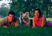 Portrait of a couple lying in the grass with their dog.