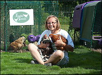 BNPS.co.uk (01202 558833)<br /> Pic: PhilYeomans/BNPS<br /> <br /> Julie and guest in the Eglu coop.<br /> <br /> Fowlty Towers - Egg-ceptional new hotel for hens.<br /> <br /> The boom in hen keeping across Britain has led a canny Kent lady to spotting a gap in the market for a deluxe hotel for punters beloved poultry whilst they jet off on their summer hols. <br /> <br /> Julie Smith from Cowden is inundated with requests for 'rooms' at 'Fowlty Towers', with customers booking months in advance to secure a spot for their prized birds. <br /> <br /> Julie's all-inclusive resort costs a poultry &pound;7 a night for each run, with round the cluck service including all food and drink.