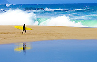 A surfer's reflection is visible as he crosses Waimea Bay beach after taking on the largest surf of the 2007-2008 big wave season.
