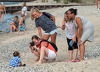 Posing a nine-month-old baby for a portrait isn't as an easy job, but with family and friends helping out in the background it's entertaining. Photographer Alina Claire reacts to baby Jordan Edwards while helping out are from left; Brooke Mullen, a family friend, mom Paula Shepley and her daughter Jaylah Henry.