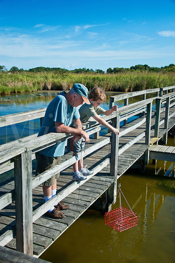 Grandfather and boy crabbing from a dock, Outer Banks, North Carolina
