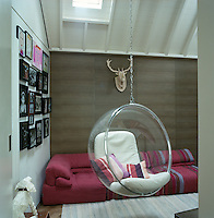 In the living room an Eero Aarnio bubble chair is suspended from the beamed ceiling and is piled with cushions