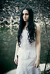 atmospheric photo of beautiful young caucasian woman looking with sadness in white dress