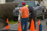 construction workers spreading asphalt with pickup in background