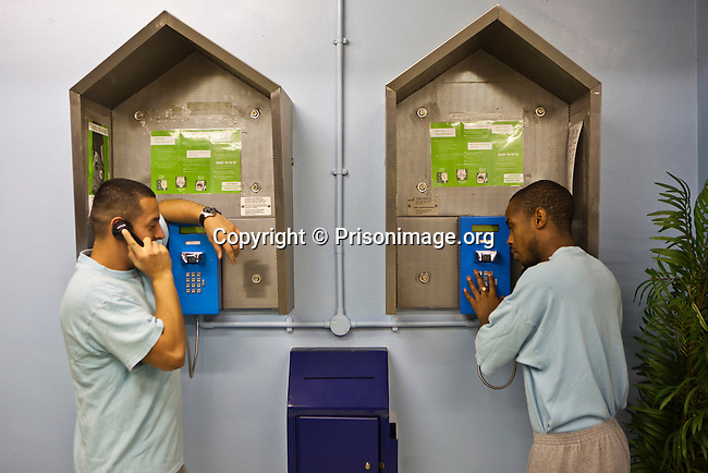 Prisoners make calls to family members from the pay phones on the E wing of HMP Wandsworth. London, United Kingdom.