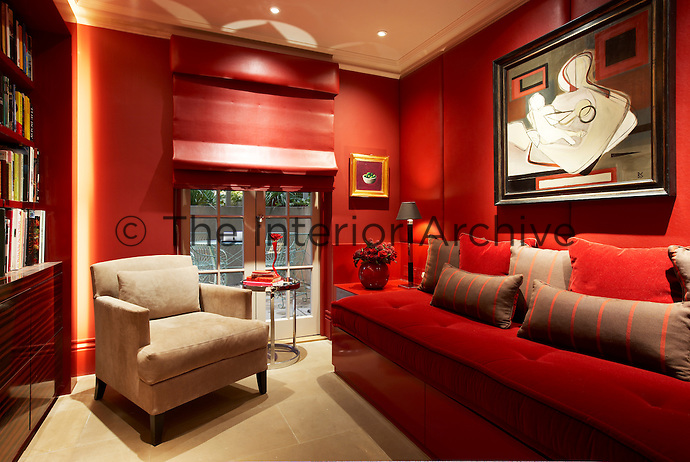 Leather-panelled walls line this library which features a red lacquered built-in banquette and contrasting beige suede armchair