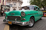 Havana, Cuba; a green and white classic 1955 Chevy is parked along the street in Old Havana