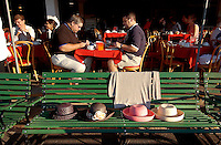 Saratoga Springs, NY  Patrons save seats with their hats in the club house of Saratoga race Course for an afternoon of thoroughbred horse racing.  The seats were saved as patrons in the background ate breakfast at the track on the morning of the Travers stakes..©Mitch Wojnarowicz All Rights Reserved