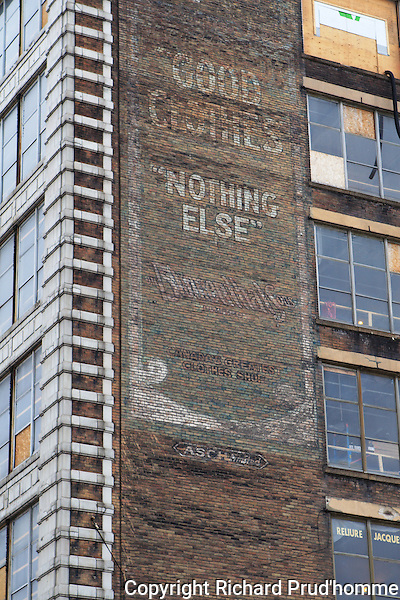 "old faded Good clothes  ""nothing else"" sign painted on side of old building in downtown Montreal  along Ste-Catherine street"
