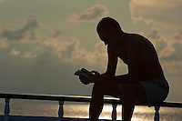 Silhouetted man reading a book on the boat deck, Maldives.