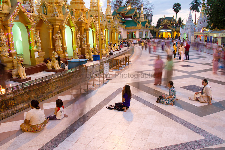 Burmese people at Shwedagon temple in the afternoon praying and cleaning