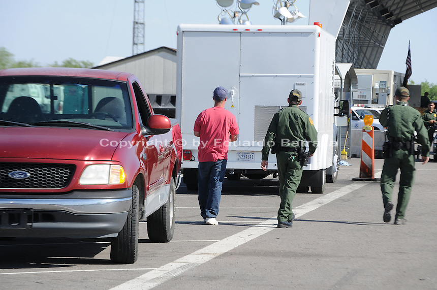 Nogales, Arizona - A motorist who was driving this pick-up truck walks next to two Border Patrol officers after being stopped for a secondary inspection. As he  is taken to an inspection station for additional questioning, his vehicle will be also subjected to an X-ray inspection using the X-ray mobile white unit seen in the background. Border Patrol checkpoints serve as inspection stations to detect illegal immigration and drug smuggling. Border Patrol agents assigned to fixed traffic checkpoints have wide discretion to stop vehicles for brief questioning and inspection of its occupants and its contents. This checkpoint is part of the Border Patrol Tucson Sector. Agent Photo by Eduardo © 2012