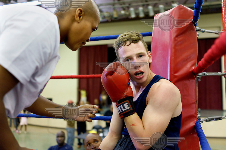Joe Eades, a young aspiring boxer, sits in the ring moments before conceding his first fight during an amateur boxing tournament in Cosmo City, a large low-income housing development 25 kms north of Johannesburg.  Julie Tshabalala, South African women's welterweight and middleweight champion, tries to encourage him.