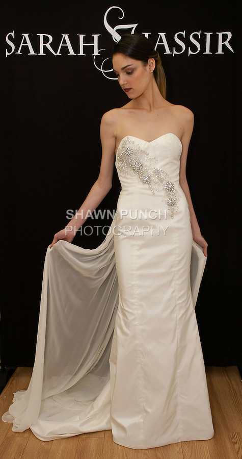 "Model poses in ""Selene"" - a strapless taffeta gown with crystal beaded applique and front slit, from the Sarah Jassir Fall 2013: From Concept To Creation collection, for her Angelique Bridal store opening at 6 East 45 Street, during New York Bridal Fashion Week, October 15, 2012"