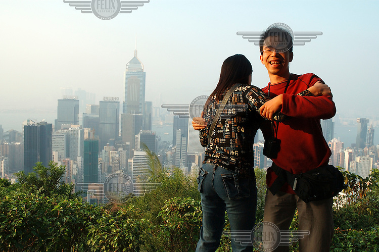 Mainland Chinese couple (more than half of all visitors come from the mainland), at Stubbs Road Lookout with its view over Hong Kong Island and its skyscrapers, with Central Plaza in Wan Chai at left.