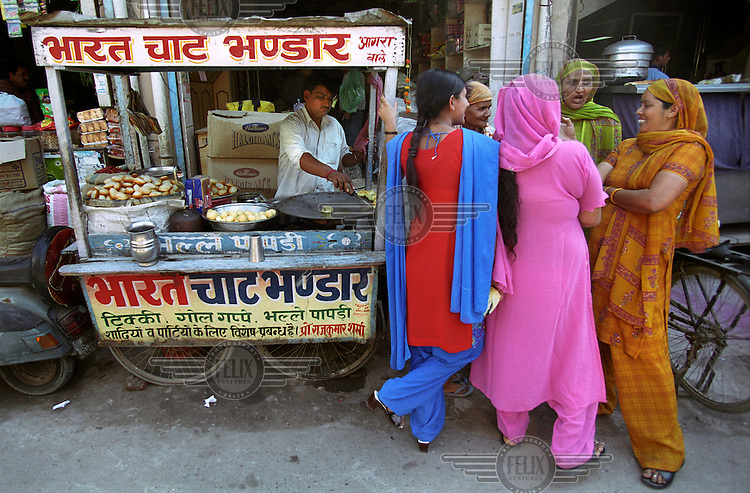 A group of women talking and laughing next to a mobile stall selling street food.