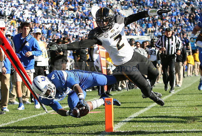 Kentucky Wildcats running back Raymond Sanders (4) gets pushed out of bounds by Missouri Tigers wide receiver L'Damian Washington (2) during the second half of the University of Kentucky vs. Missouri University football game at Commonwealth Stadium in Lexington, Ky., on Saturday, November 9, 2013. Mizzou won 48-17. Photo by Tessa Lighty | Staff