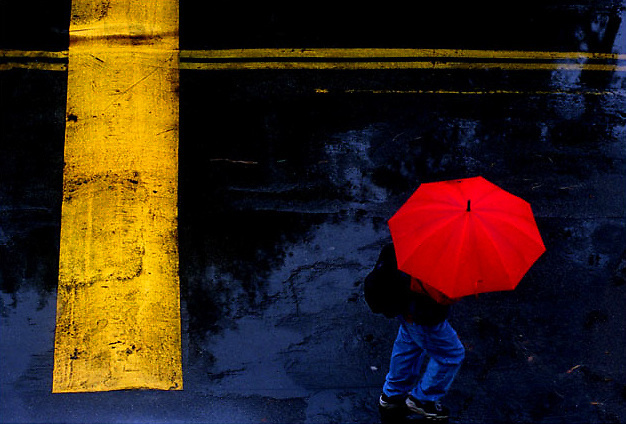ME.Rain Art.Red.RH--012500--Toting a bright red umbrella, a student becomes part of a colorful graphic as he makes his way past a speeedbump while crossing campus in the rain at Saddleback College, Tuesday morning in Mission Viejo. .Photo/Art by:Richard Hartog