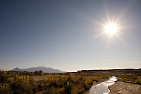 The Henrys Mountains silhouette behind the Dirty Devil River and the desert landscapes of the Colorado Plateau in southern Utah. The range was the last discovered in the continental United States, on the second Powell expedition in the 1870s.
