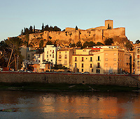 Houses of the old city of Tortosa along the right bank of the Ebro river, with the castle of Sant Joan or La Suda on the hill behind, Tortosa, Tarragona, Spain. The castle was built in the 10th century under the muslim Caliph Abd ar-Rahman III and has been a royal mansion since the 13th century. Picture by Manuel Cohen