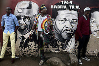 SOWETO, SOUTH AFRICA: Designers Lethabo Tsatsinyane, age 29 and Sibu FDB, age 29, stands next to a Nelson Mandela mural outside Regina Mund Catholic church in Soweto, South Africa.  Soweto is South Africa's largest township and it was founded about one hundred years to make housing available for black people south west of downtown Johannesburg. The estimated population is between 2-3 million. Many key events during the Apartheid struggle unfolded here, and the most known is the student uprisings in June 1976, where thousands of students took to the streets to protest after being forced to study the Afrikaans language at school. Soweto today is a mix of old housing and newly constructed townhouses. A new hungry black middle-class is growing steadily. Many residents work in Johannesburg, but the last years many shopping malls have been built, and people are starting to spend their money in Soweto.  (Photo by Per-Anders Pettersson)