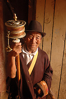 A Buddhist pilgrim spins his prayer wheel in the doorway of the Jokhang Temple in Lhasa, Tibet. The Jokhang is the holiest of all holy places in Tibet, and many Tibetans travel days, months, and even years, on pilgrimage to Tibet's most sacred Temple..