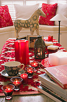 The coffee table in the living room is decorated with tealights and candles to create a festive mood