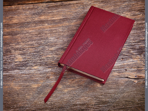 Red hardcover book on wooden table background
