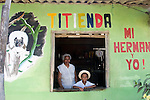 """Titi""- (little monkey in Spanish) enda. The owner with her grandson tending their small grocery store in Los Limites, Colombia. Advertising the presence of the cotton-top tamarin in their forests helps educate the community and is good for business."
