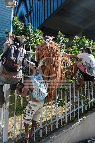 Brazilian indigenous men climb the fence at BNDES, the Brazilian National Development Bank. They had marched in protest from the People's Summit at the United Nations Conference on Sustainable Development (Rio+20), Rio de Janeiro, Brazil, 18th June 2012. Photo © Sue Cunningham.