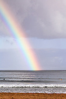 Morning surfers take in a rainbow at Hanalei Bay, as seen from Hanalei Beach, Kaua'i.