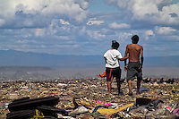 A Nicaraguan couple of garbage recollectors walks in the garbage dump La Chureca, Managua, Nicaragua, 4 November 2004. La Chureca is the biggest garbage dump in Central America. Hundreds of trash recollectors search in tons of smouldering garbage mainly metals (copper, aluminium), others concentrate on glass which is cheap, but in bigger amount. The majority of the recyclers are families with children for whom recycling is a regular job. The children very often eat the food they find on the dump, none of them goes to school, they suffer from skin diseases, they have high levels of lead and DDT in blood.