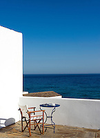 A director's chair and a table positioned on a terrace looking out to sea