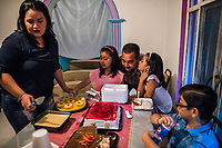 Carlos Saldana, leans between Vicky Delgadillo's grandchildren, Regina (L) and Renata (R), as they attend a birthday party and family gathering at the house of Vicky's daughter in Xalapa, Mexico on November 4, 2017. <br /> Photo Daniel Berehulak for The New York Times