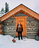 FINLAND, Artic, Nunnanen, Mature woman standing in front of husky farm