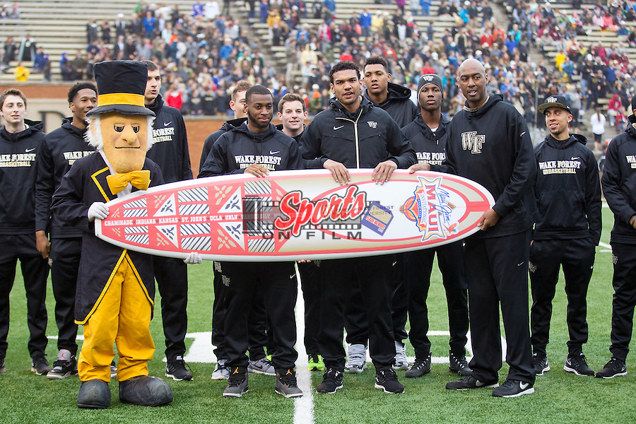 The Wake Forest Demon Deacons men's basketball team are presented with a custom surf board from the Maui Invitational tournament they will participate in during a timeout at the football game at BB&T Field on October 3, 2015 in Winston-Salem, North Carolina.  The Seminoles defeated the Demon Deacons 24-16.   (Brian Westerholt/Sports On Film)